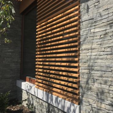 Kamenný obklad a dřevěné žaluzie